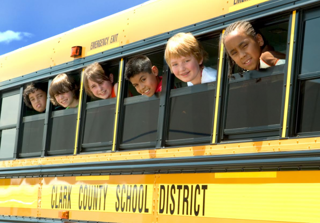 children popping their heads out of the windows of a school bus