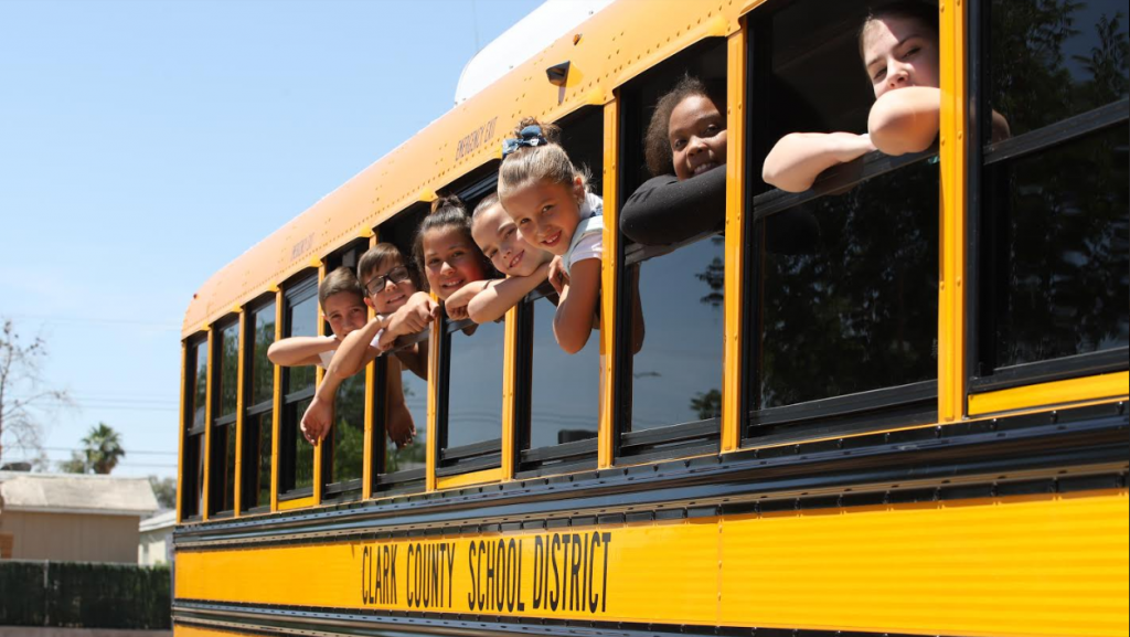 smiling children popping out of the windows of a school bus