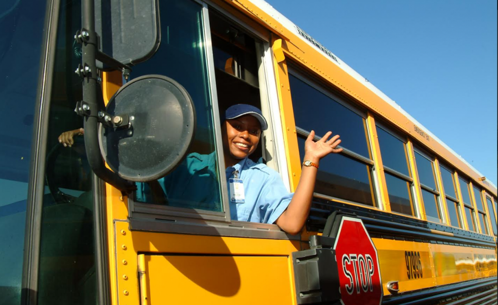 a bus driver waving out of the driver window of a school bus